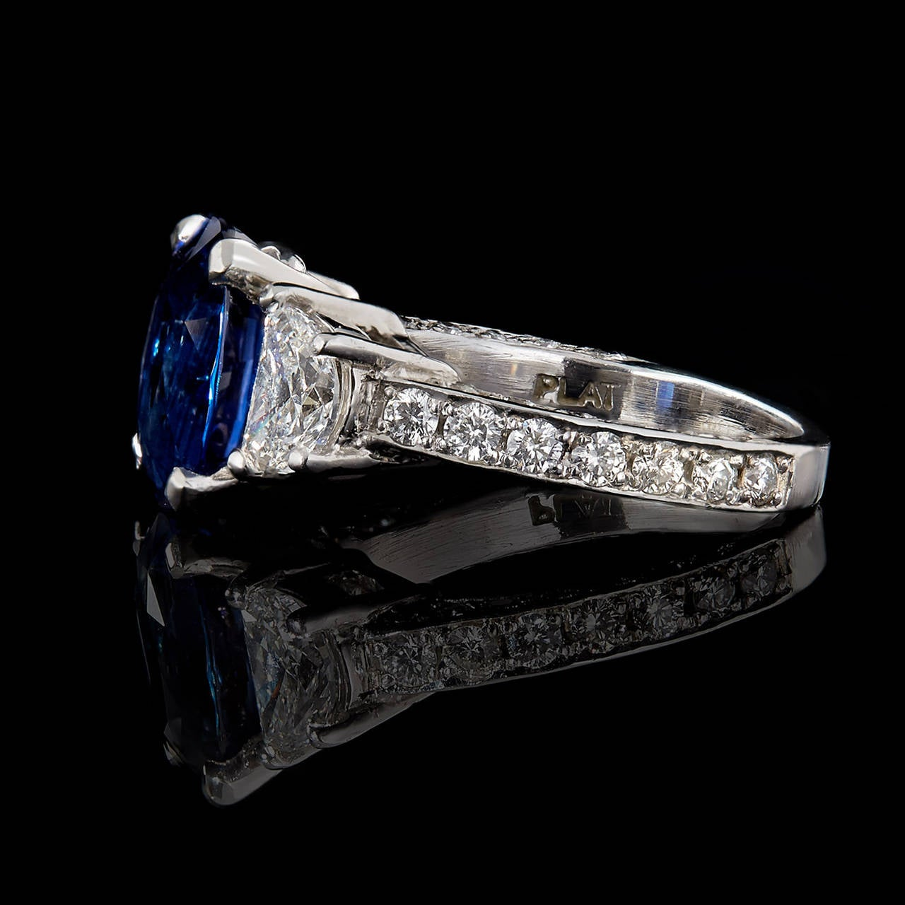 3-Stone No Heat Vivid Blue Sapphire from Madagascar & Diamond Ring set in Platinum. The center stone is a 4.07 carat oval mixed cut blue sapphire flanked with half-moon shape brilliant cut diamonds on each side totaling 1.60 carats and 38 Round