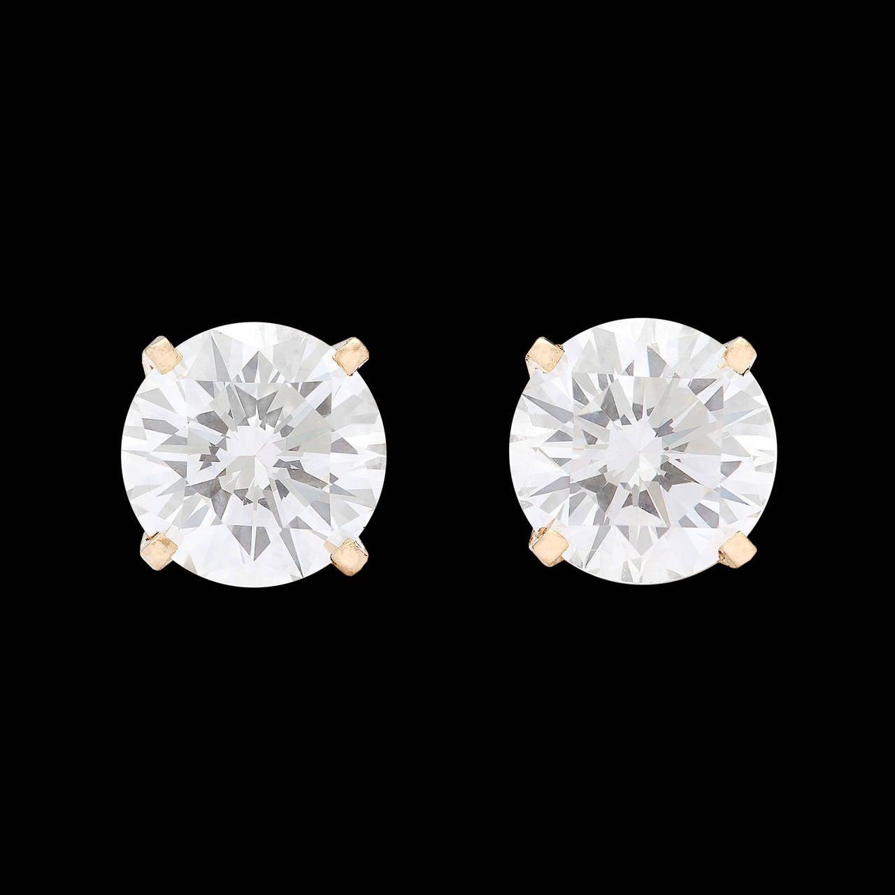 Classic Round Brilliant Cut Diamond Stud Earrings set in 18Kt Yellow Gold 4-Prong Basket Settings with Posts and Friction Back Closures. Each 1.02-ct diamond is accompanied by a GIA report and graded E color and VVS2 clarity. The total weight for