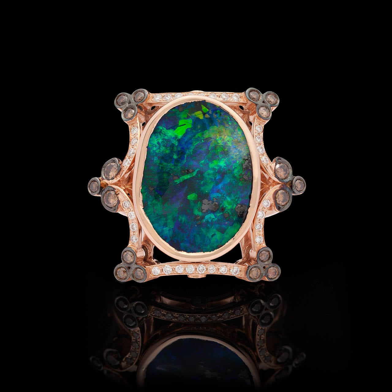 18Kt Rose Gold ring features a 7.23-ct Oval shape Boulder Black Opal with blue & green Play of Color. Accenting the ring are 32 white diamonds totaling 0.20-ctw, and 18 cognac color diamonds totaling 0.30-ctw. The top of the ring measures about 1