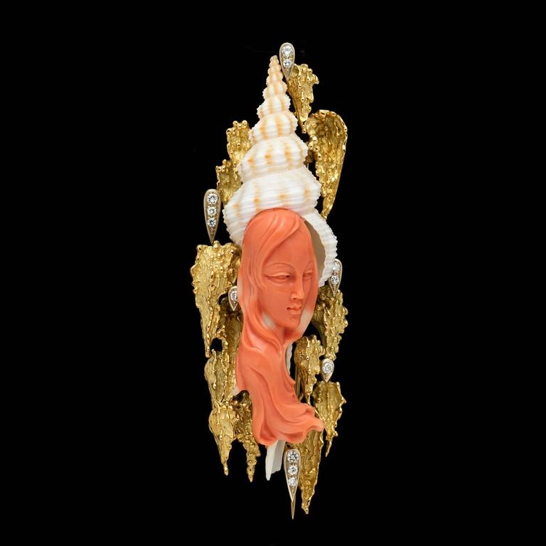 This fantastic piece of art features a carved coral portrait of a young woman on a 18k yellow gold brooch adorned with approximately 0.44 carat total weight of round brilliant cut diamonds. The coral figure is elegantly placed with the seashell