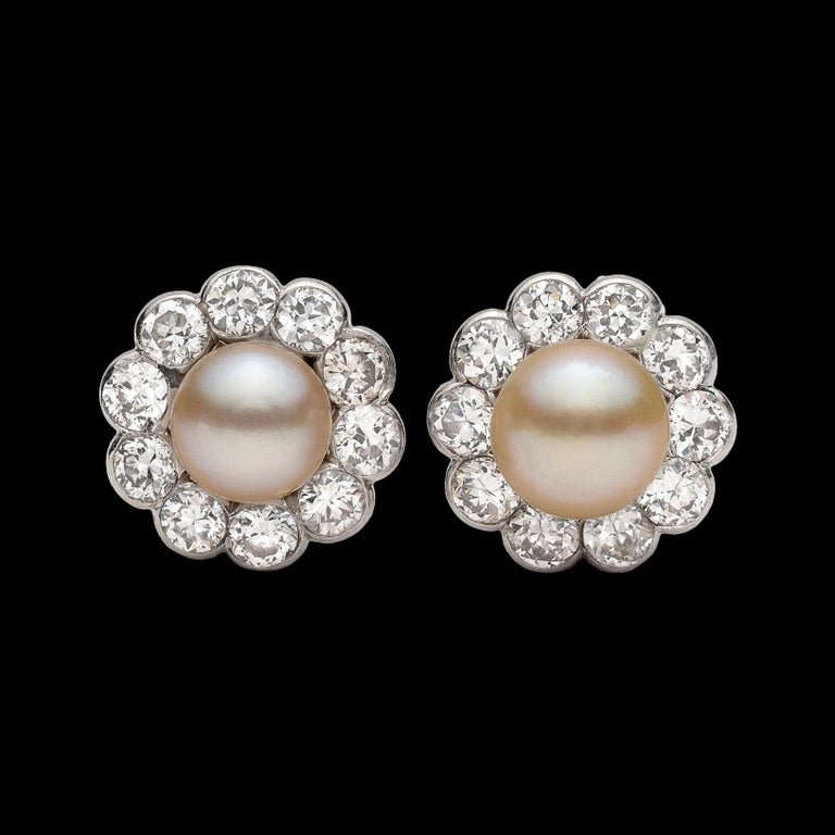 Circa 1915, the platinum earrings center two button-shaped pearls, measuring approximately 6.85 and 6.15mm each, framed with 20 round-cut diamonds weighing in total an estimated 1.20cts. Weighing 7.0 grams and measuring 3/8in. in diameter, the stud