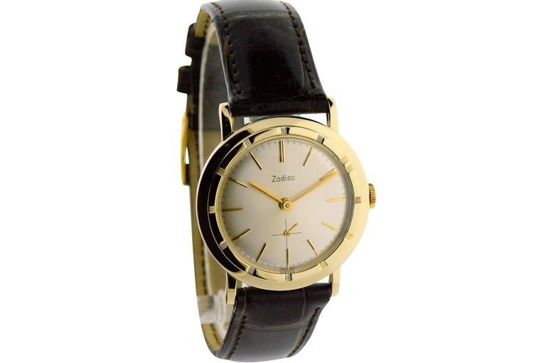 FACTORY / HOUSE: Zodiac Watch Company STYLE / REFERENCE: Round / Moderne METAL / MATERIAL: 14kt Yellow Gold DIMENSIONS:  37mm  X  32mm CIRCA: 1950's MOVEMENT / CALIBER: Winding / 17 Jewels / Cal.36  DIAL / HANDS: Original / Silver Batons / Baton
