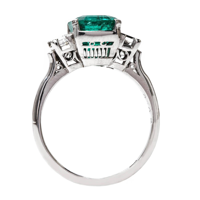 bold modern era emerald ring with square step cut diamonds
