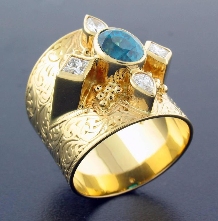 This ring was designed and made by well known designer Paula Crevoshay.  It contains a Natural Blue Zircon weighing 2.80 carats, and Diamonds weighing 0.52 carats.  It is made entirely in 18k yellow gold  The size is approximately a 7 1/2 ~ 8.  Wide
