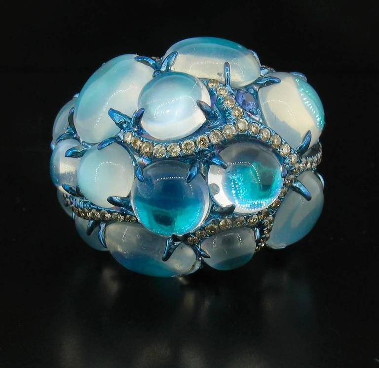 Designed by famed designer Arunashi, This hand made, extraordinary ring features Cabochon Blue Moonstones of the highest quality weighing 16.49 carats total.  They are interwoven with Diamonds weighing 1.06 carats G-VS2 in color and clarity, and