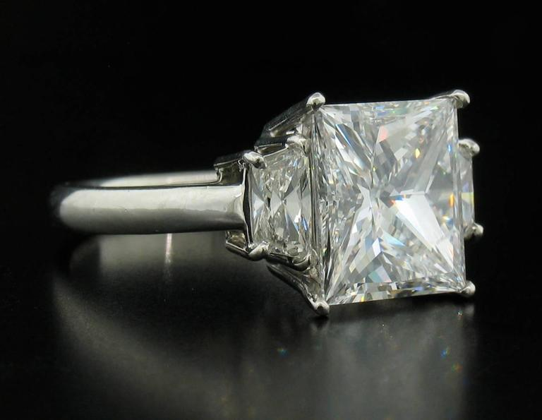 This is a beautiful Diamond Ring with a 4.03ct Princess center stone.  This is an ideal cut stone, hand selected by us.  It is an E - VS2 with a GIA laboratory report.  Two trapazoid Diamonds flank the sides of the center stone and weigh a total of