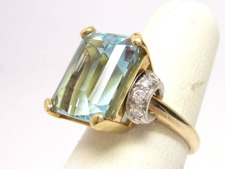 This vintage 1950s ring features a stunning 10-carat Aquamarine with lush blue color, set into a gorgeous buttery-yellow 14K gold mounting. On both sides are platinum accents set with diamonds (~1/3cttw).  This vintage ring is in excellent