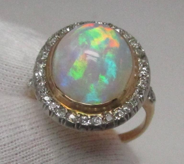 This Edwardian platinum over 18 karat gold ring features an impressive 6.06 carat opal cabochon surrounded by 32 Old Mine Cut diamonds with two more on the shoulders, equaling 1.00 carat total weight. The combination makes for a stunning presence.