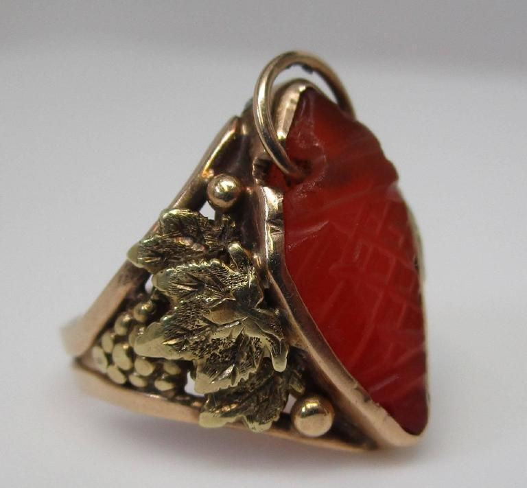 This wonderful 14K yellow gold ring is from the 1910 Arts and Crafts period. It features a craved carnelian with a loop though one end and grapes with leaves on the shoulders. It is not broken, it shows dissimilar oxidation as the solder was a