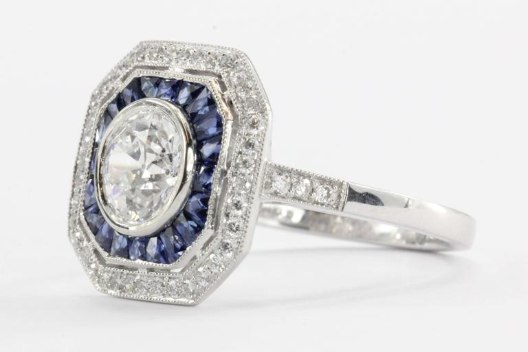 Brand New Sophia D Art Deco inspired platinum set diamond and sapphire engagement ring. The center stone is a genuine antique diamond.  The diamond is an old European cut 1.02 carat, E color, I1 clarity. The center stone is GIA certified and come