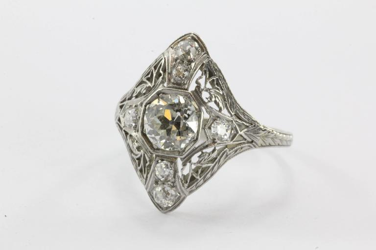 Antique 1.5 ctw Diamond Art Deco Platinum Engagement Ring. The ring is in excellent estate condition and ready to wear. The center stone is an approximately 1.01 carat old European cut diamond with J color and Vs2 clarity. There are an additional 6