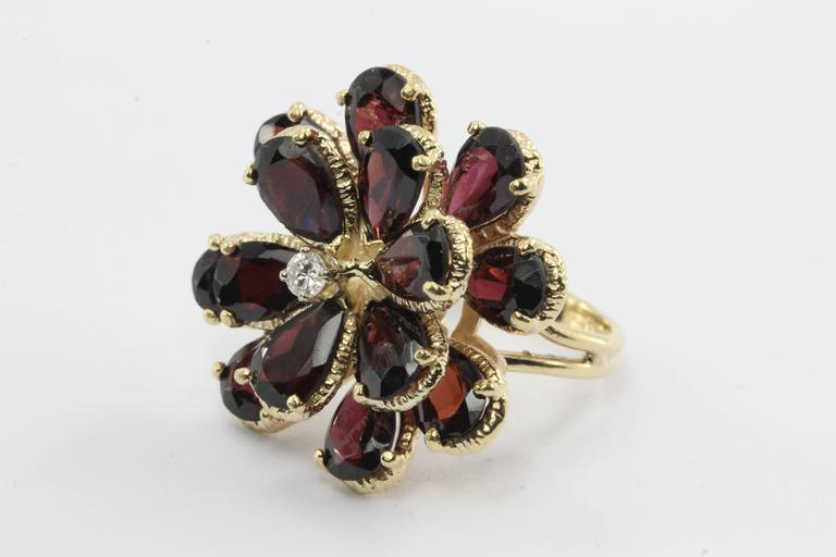 A retro floral garnet & diamond ring in 14k yellow gold circa 1950. This gorgeous vintage ring holds a stunning array of deep rich pear shaped garnets. There are 14 garnet petals in total. The stones are each approximately 8 MM in length and 5 MM in
