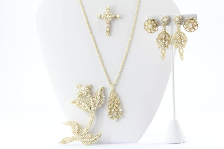 This collection is in excellent antique estate condition and ready to wear. The collection consists of 5 articles of jewelry. Two brooches, a necklace with pendant and two pairs of earrings. The pieces are made of Seed Pearls sewn over carved mother