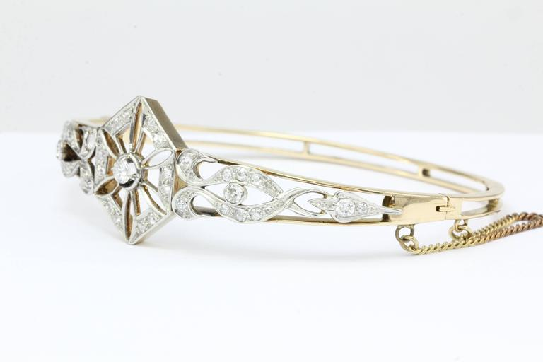 Art Deco 14K Yellow Gold Old European Cut Diamond Bangle Bracelet c.1920  A delicate art deco sparkling diamond snowflake appears to be tossed by opposing east & west winds as this magical scene plays out atop this stunning bracelet. The piece