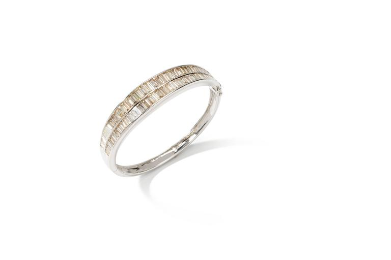 Designed with two rows 77 baguette-cut diamonds weighing 10,81 ct. Mounted in 18 carat white gold. Hallmarked inside: 750, DG in quadrat.  Total weight: 29,77 grams. Measurements: 1.97 x 2.28 in ( 5 x 5,8 cm )