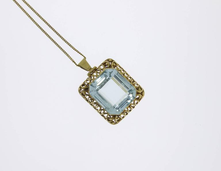 The classic pendant consist of 14 K yellow gold and shows a large emerald-cut aquamarine weighing circa 38 ct. Marked with the purity 585 on the loop.That can also be worn as a brooch. Total weight: 23,16 g. Dimensions of pendant: 1.26 x 1.1 in (