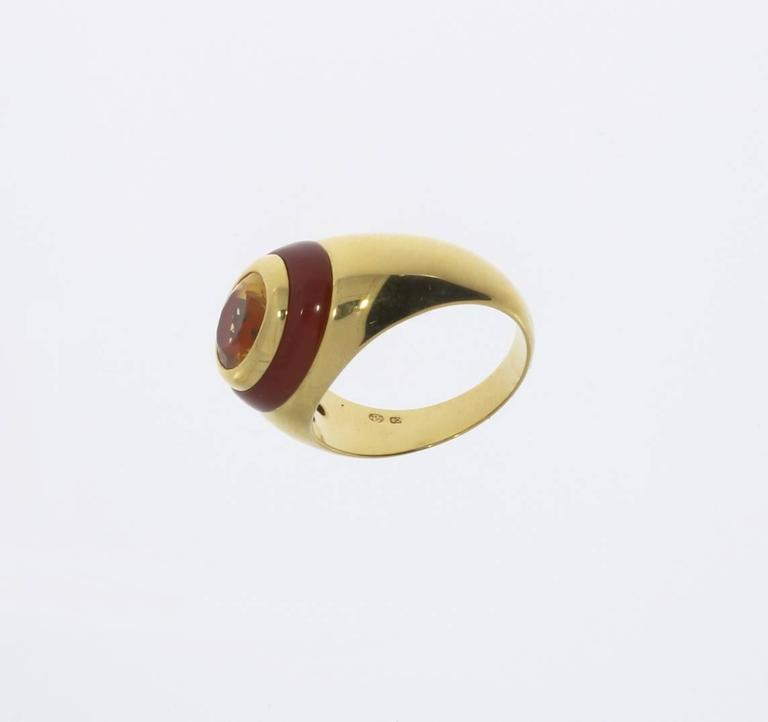 Set with oval shaped citrine in bezel setting edged by carnelian band and mounted in 18 K yellow gold. Hallmarked inside with the purity 750 and OE. Total weight: 14,52 g. Height: 0.35 in ( 0,9 cm ) Ring size: 65 ( US 11 )