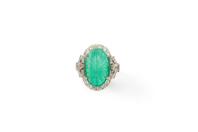 Art Déco Ring with carved oval shaped Colombian emerald cabochon weighing 10,12ct. Surroundet by 42 old-cut diamonds with a total weight of 0,90ct. Mounted in platinum. Hallmarked inside with the purity 950. Total weight: 7,46 g. Ring size: 53 (