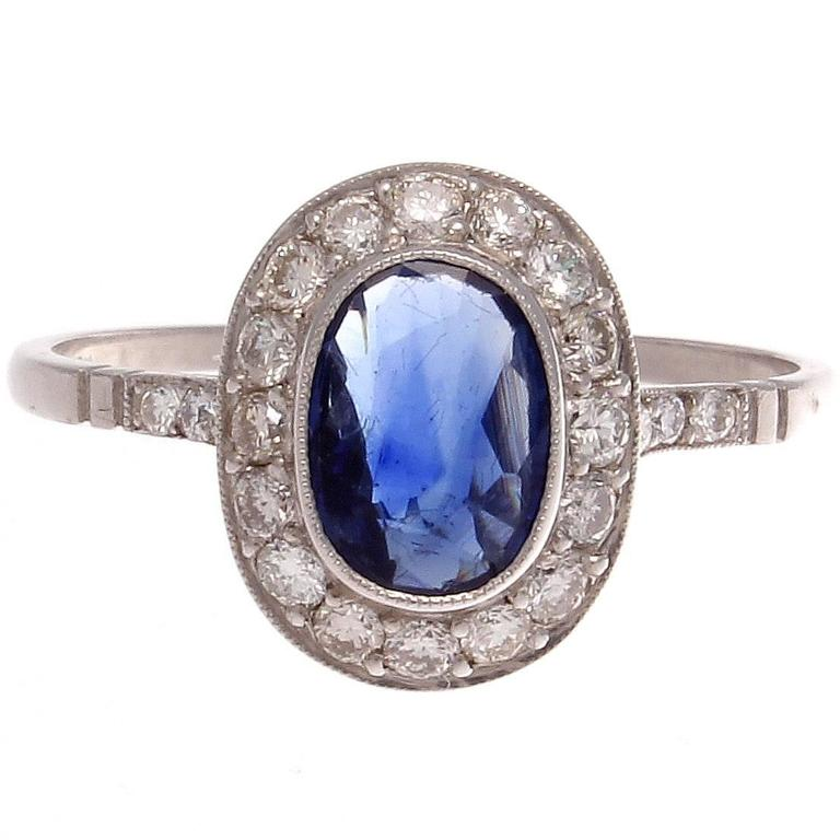 Forever in style, the classic halo ring. Featuring an approximately 1.00 carat deep blue oval cut sapphire elegantly surrounded by a  halo of colorless diamonds. Expertly hand crafted in platinum.  Ring size 7 and may be resized.