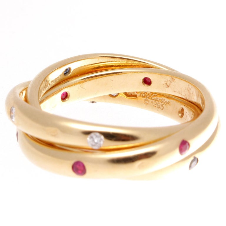 Cartier, elegant and timeless. A modern rendition of the harmonious trinity ring that has been part of the Cartier family since 1924. Designed with lively rubies, sapphires and diamonds. Crafted in 18k yellow gold.   Ring size 6-1/4