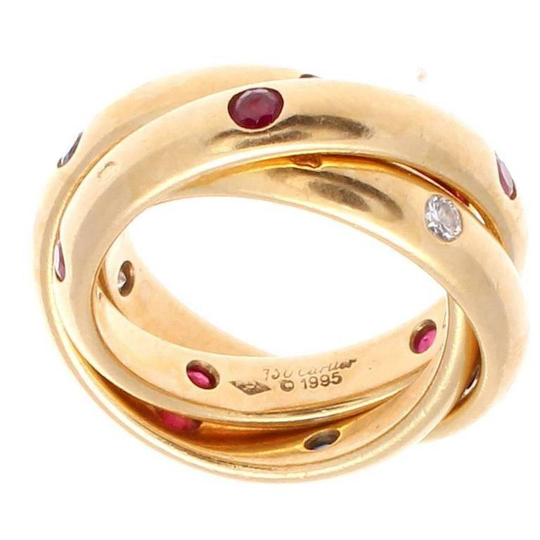 Cartier, elegant and timeless. A modern rendition of the trinity ring that has been part of the Cartier family since 1924. Designed with lively rubies, sapphires and diamonds. Crafted in 18k yellow gold.     Ring size 4 3/4.