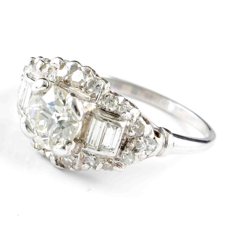 An orchestra of design is directed by geometric shapes formed by diamonds. Featuring an approximately 0.90 carat old European cut diamond surrounded by round and baguette cut diamonds. Hand crafted in platinum.  Ring size 7 and can easily be resized
