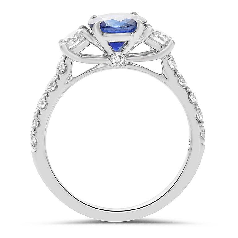 Three stone Sapphire and Diamond ring with ornate carving and intricate gold work and diamond accents. Diamond accents one-quarter of the way down the shank. Ring is evocative of Art Deco designs that used a combination of Sapphires and Diamonds.