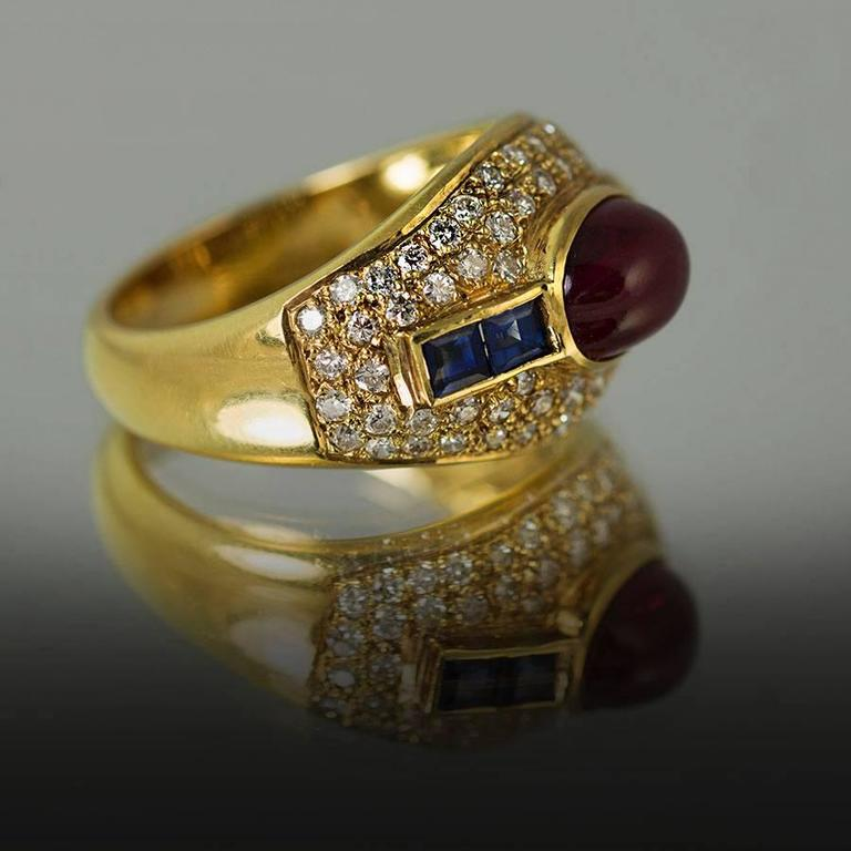 18K Ring with 1 oval cabochon Ruby weighing 2.77 carats and 4 square cut sapphires weighing 0.57 carats and 28 pave set round brilliant diamonds weighing 0.72 carats.
