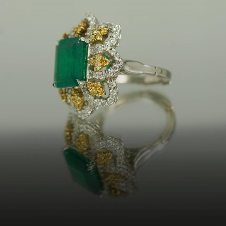 Platinum ring with 1 Colombian Emerald weighing 5.84 carats and 64 white round brilliant diamonds weighing 1.28 carats and 32 intense yellow round brilliant diamonds weighing 0.64 carats. Size 5 (Free Sizing)