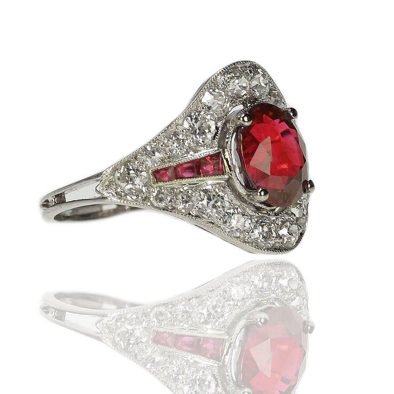 Fabulous platinum Art Deco ring with AGL certified 2.18 oval carat Burma Ruby and six square rubies weighing approximately 0.50 carats and approximately 1.25 carats of high quality old euro cut diamonds.