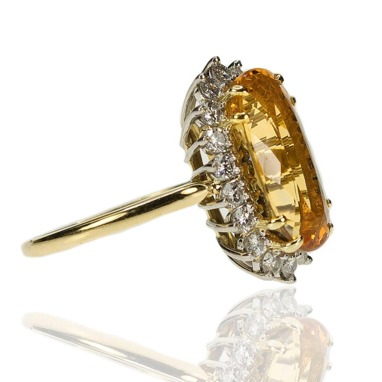 18k & Platinum Ring with approximatel 8.50 carat Imperial Topaz and 18 modern round brilliant diamonds weighing approximately 1.00 carats/ 8.02g