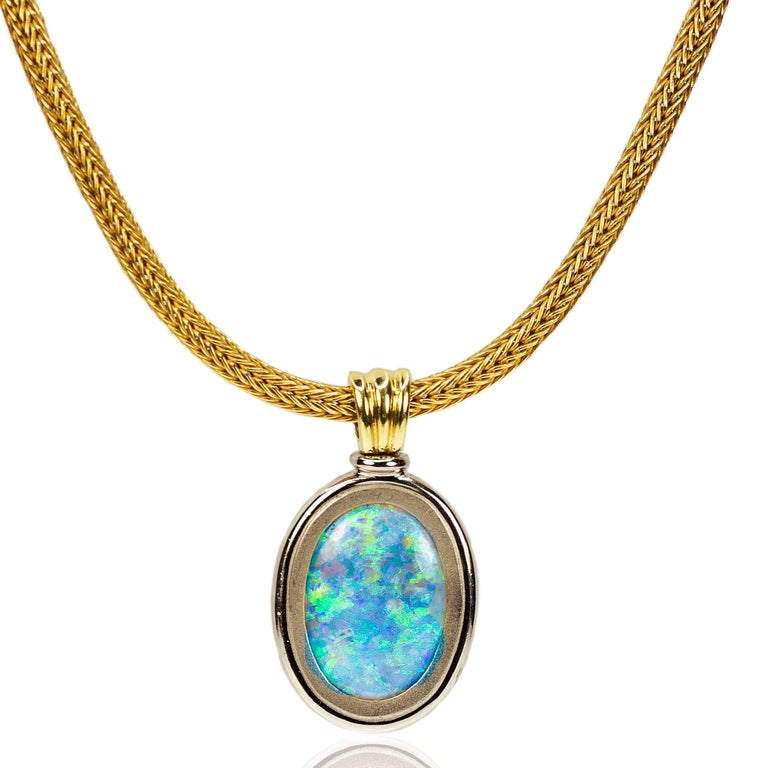 Magnificent Necklace with reversible double sided Australian Opal weighing approximately 15 carats and displaying gorgeous blue, green and red flashes of color. Set in 18k and floating on a thick 18k mesh chain. 61.42 grams.