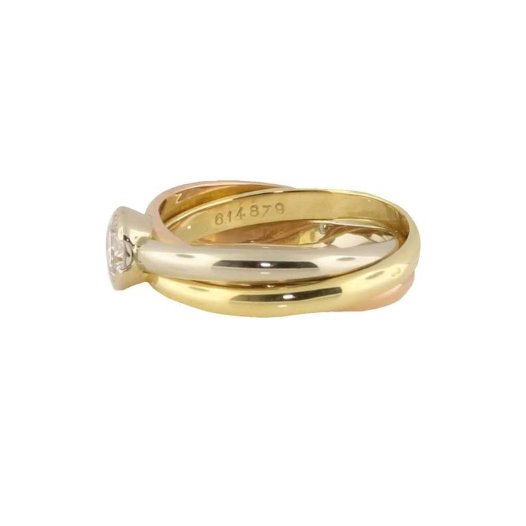 This ring is the definition of Cartier. It is classy, elegant and a true image of Cartier's fashion. This tri-colored rolling ring has the normal white, yellow and rose gold bands interlocking but is also adorned with a solitaire diamond. The size
