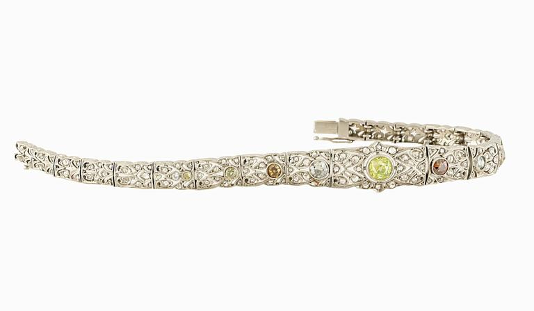 A timeless 18kt art-deco bracelet with intricate detail and workmanship . There are 9 exquisite NATURAL colored diamonds. The colors range from shades of yellow, oranges and blue.  The center stone is about +/- 0.50ct.  small white diamonds total