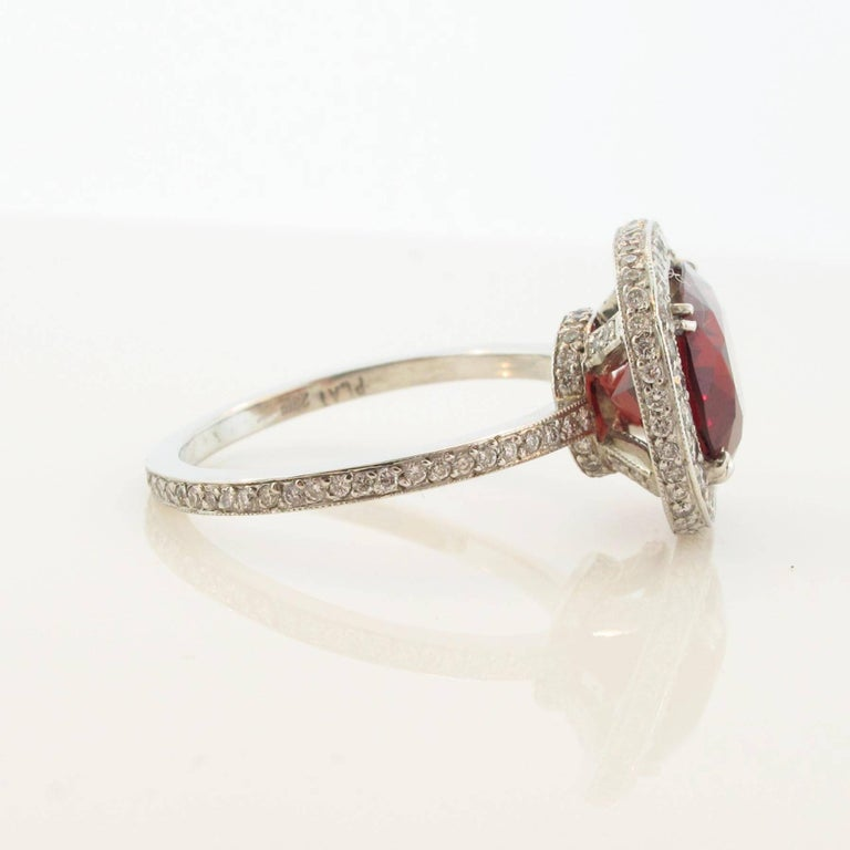 A spectacular diamond, and Spinel platinum ring. The 3.40 carat Spinel is the optimum deep red color one would desire in a ring like this. This easy to wear ring can be dressed up or dressed down for any occasion. The band has pave diamonds on both