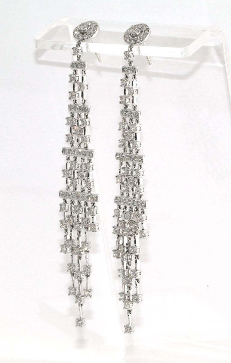 Trendy pair of 14 Kt white gold and diamond earrings. They hang at the perfect length with over 100 diamonds, weighing ~4.25 ctw. They can be worn day or night and will become a favorite pair you will never want to take off. Chandelier earrings the