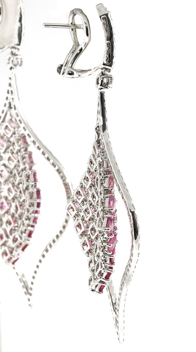 Gorgeous pair of hanging pink sapphire and diamond drop earrings. The greatest part is how perfectly the pink sapphires graduate in color from deep pink to light pink. The center section of the earrings hangs freely so there is flexible movement.
