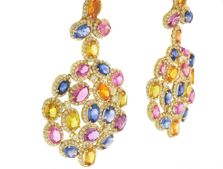 These bright, bold and colorful chandelier earrings are set in 18 Karat Yellow Gold. They are made with 36.85 carats of multi colored sapphires and 7.87 carats of diamonds.   Earrings measure 6.5 cm long x  3.75 cm wide.