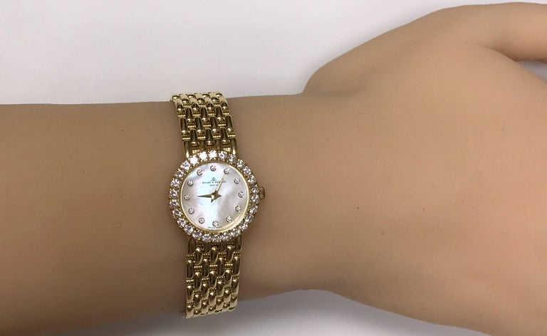 Mother of pearl diamond dial and bezel 18 Karat yellow gold Baume Mercier wrist watch.  Woven textured and high polish bracelet.  38 round diamonds approximately 1.00 carat total weight VS, G. 27.6 dwt. Clasp closes firmly, no stretch in the