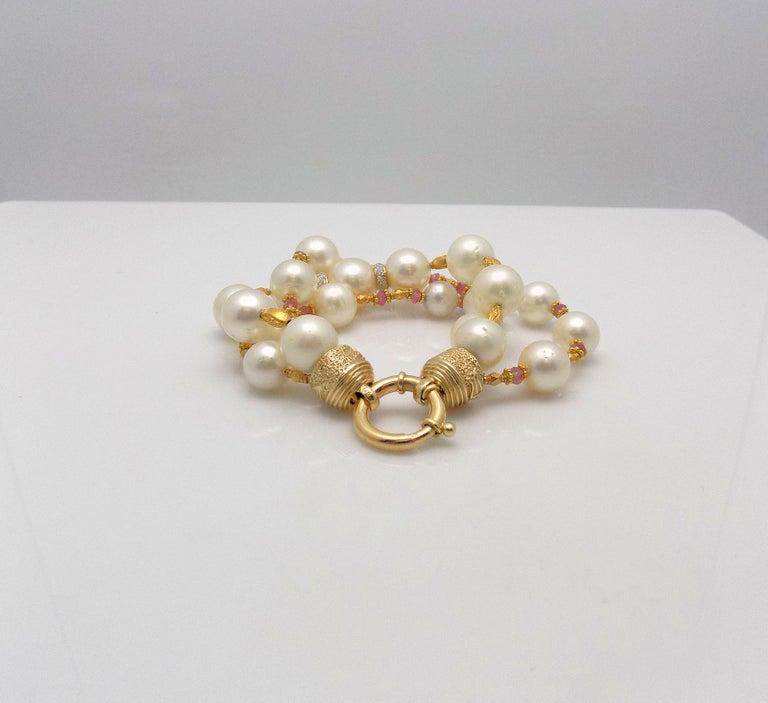 Glamorous 3 Strand South Sea Cultured Pearl Bracelet with 2 Diamond Rondelles 0.10 Carat Total Weight; Faceted Pink Tourmaline Beads; 18 Karat Beads and 14 Karat Large Spring Ring Clasp; 8
