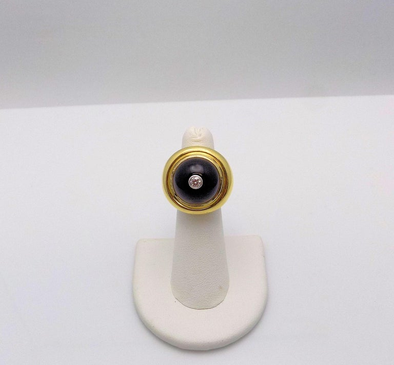 Classic 18 Karat Yellow Gold and White Gold Black Onyx and Diamond Ring featuring (1) 15.5 MM Round Cabochon Cut Black Onyx; 1 Round Brilliant Diamond 0.15 Carat, VS, H; the ring face measures 25 MM Diameter; Finger Size 6; Signed: Tiffany & Co