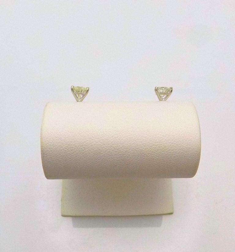 Pair 14 Karat White Gold Diamond Earrings, Martini Setting featuring 2 Round Brilliant Diamonds 1.60 Carat Total Weight; SI-3, J-K; Sterling Silver Backs, 1.0 DWT or 1.56 Grams.