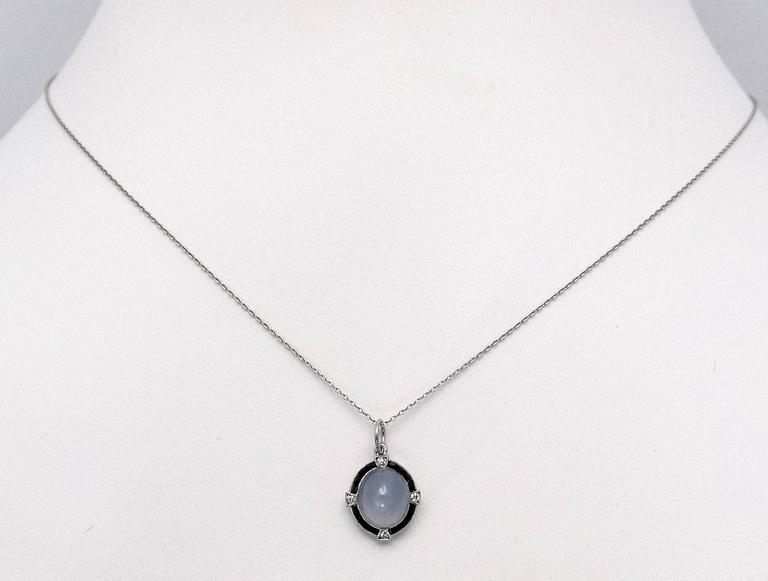 Antique Art Deco Platinum pendant weighing 3.33 carats, set with four Swiss round cut diamonds and channel set calibre' black onyx.  Diamonds weigh 0.05 carat total weight of grade VVS-2, G.  Platinum curb chain is new, 18 inches long.  c. 1920. 2.1