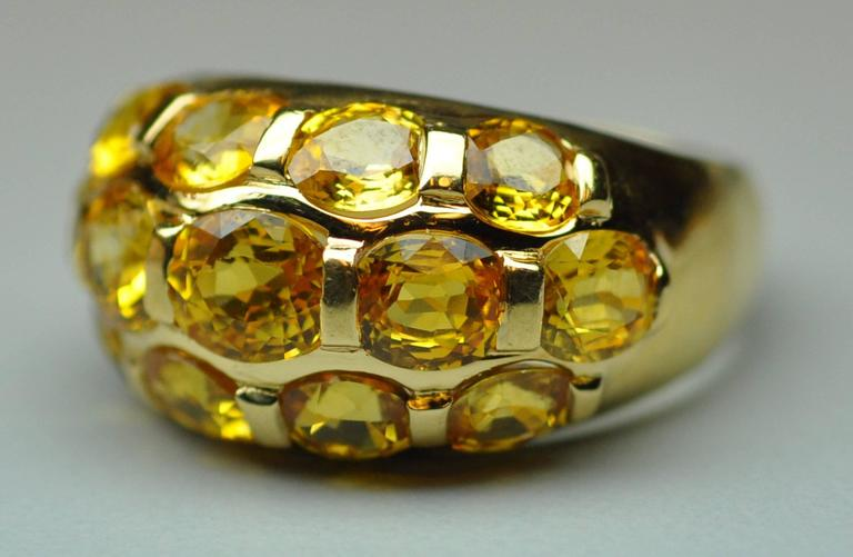 18 Karat yellow gold dome ring set with 13 oval cut matched yellow sapphires weighing a total of approximately 7.00 carats.  Sunny, bright yellow color, well-matched, excellent clarity.  5.6 dwt. Milan gold marks.