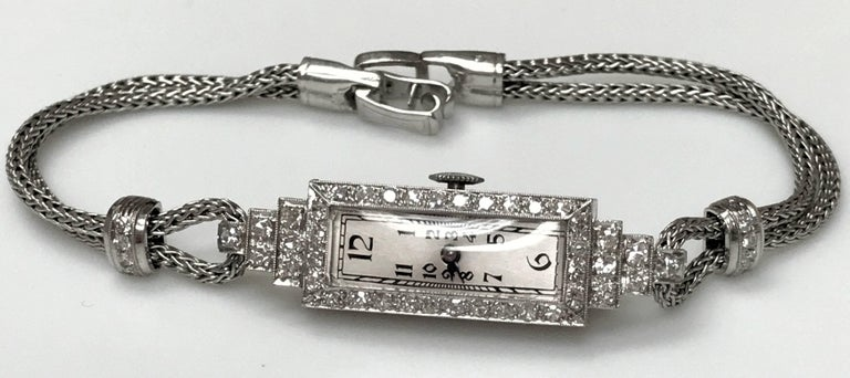 """All platinum: case, band, and diamond set fittings. This long, thin style of watch case is called """"baguette,"""" reminiscent of the baguette cut diamond, which was most used in the Art Deco period. White dial appears to be original and in"""