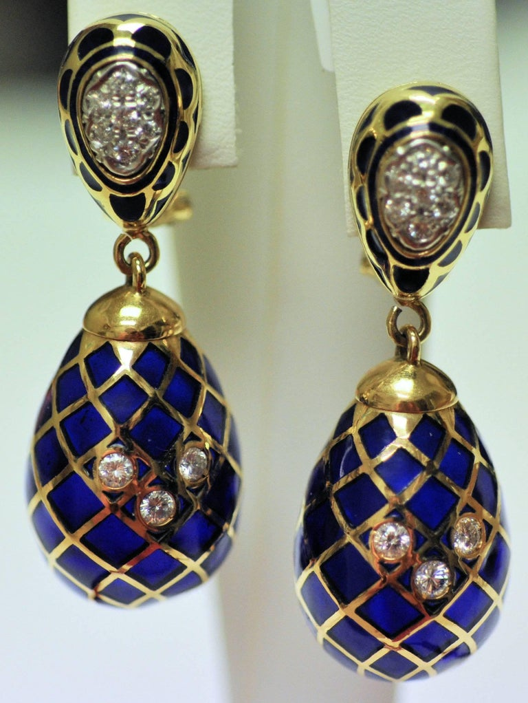 """Plique a jour means """"letting in the light"""" in French and these certainly do.  The blue enamel is translucent between the grid of gold, and beautifully reflects the light when worn.  The top and center bottom are set with diamond accents. There are"""