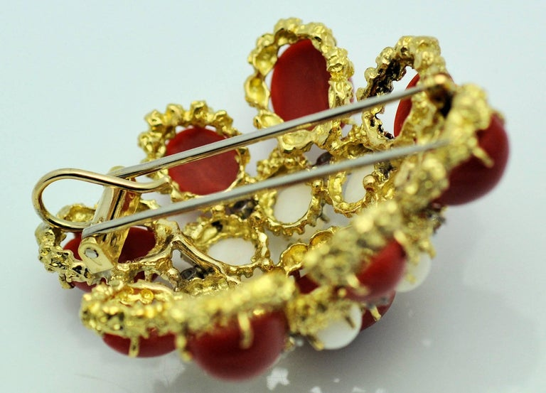 A lovely mid-century piece of textured jewelry capturing the best of the period.  Fine white and deep red coral stones and fine round diamonds.  This piece can be worn as a brooch with double prong clip-hinge or added to a gold necklace to make a