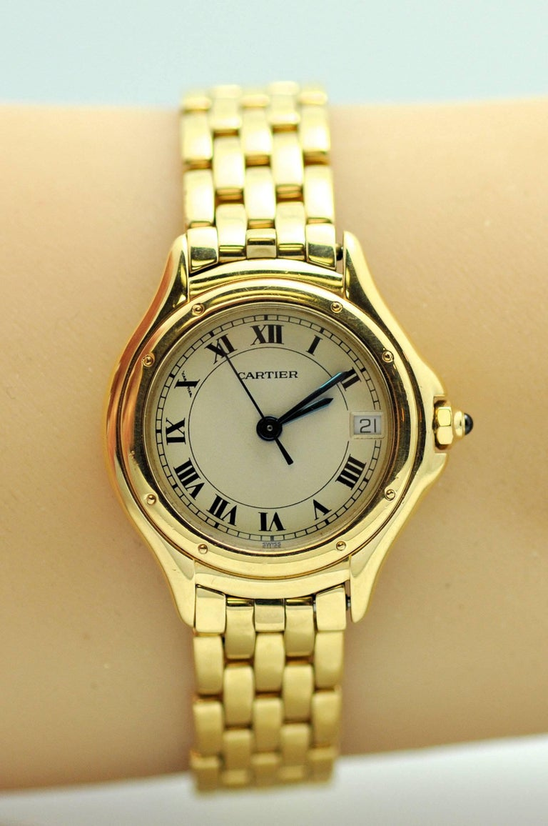 18 Karat yellow gold lady's Cougar model wrist watch.  Cream color dial with Roman numerals and date.  Synthetic sapphire dial.  Quartz. Double deployant clasp. Watch length can be reduced.