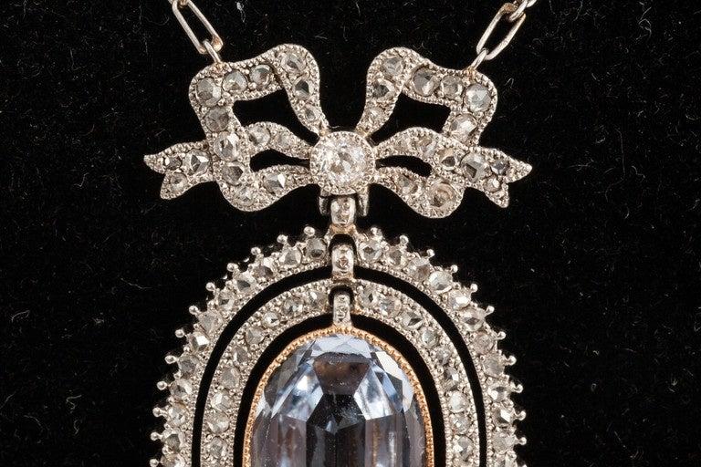 Elegant Edwardian Natural Ceylon Sapphire with Diamond surround set in Platinum on a fine chain