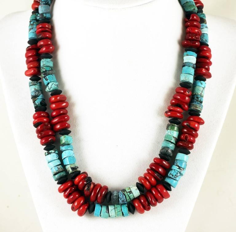 Double strand of natural Arizona Turquoise rondels and polished gemmy slices of  red Bamboo Coral accented with black Onyx rondels Size:  Coral varies approximately 12 mm Length:  18 inches Clasp:  silver tone